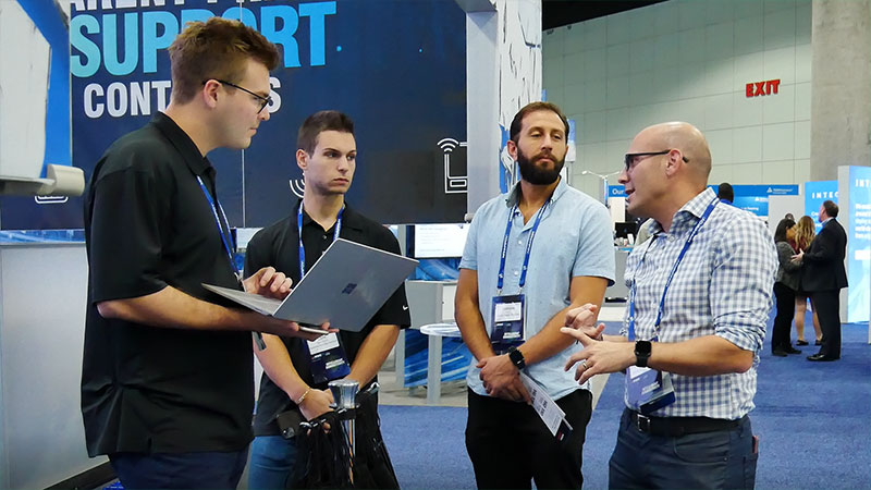 SIMON IoT employees meet with potential customers outside booth at tradeshow in California